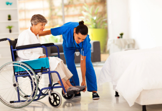 caregiver fixing the shoes of a patient sitting on a wheelchair
